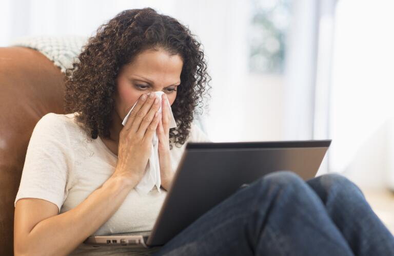 Portrait of woman sitting with laptop and blowing nose