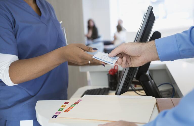 patient handing nurse health insurance card