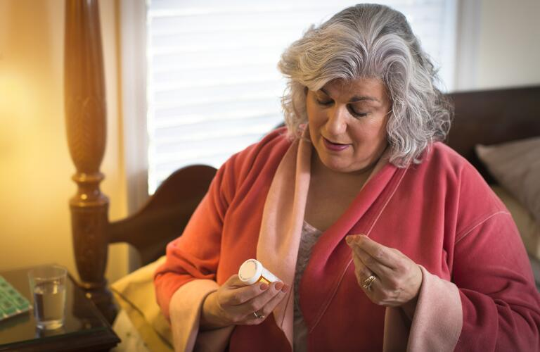 Mature woman sitting on bed reading information on pill bottle