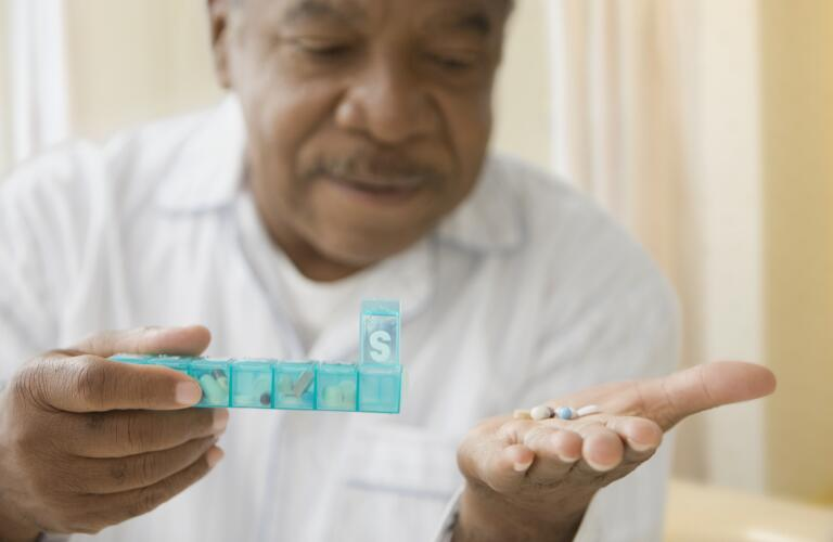 Older African American man taking pills out of weekly pill box