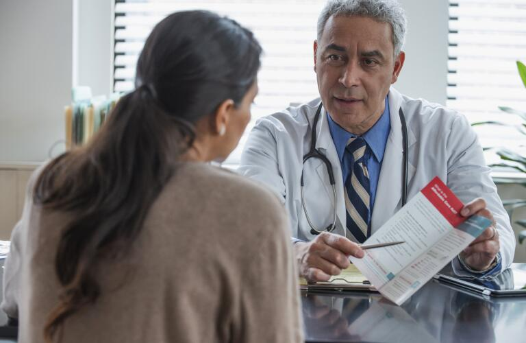 Hispanic doctor explaining pamphlet to client in office