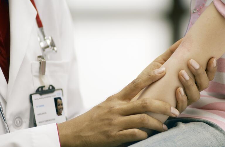 doctor examining girl's rash on her inner elbow