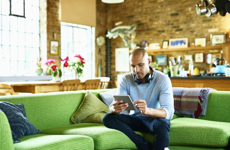 man using tablet while sitting on bright green couch in living area