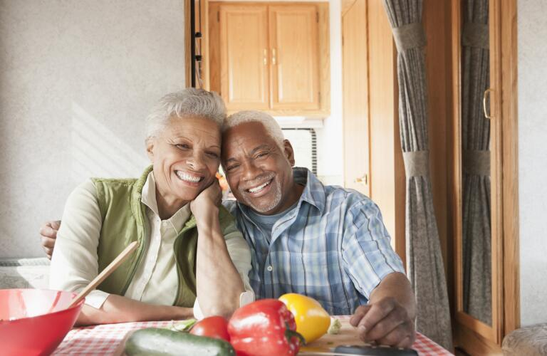 senior couple sitting at dinner table in front of healthy food