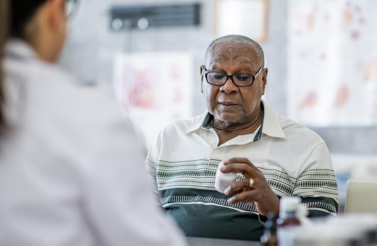 Senior African American male patient holding prescription bottle with doctor