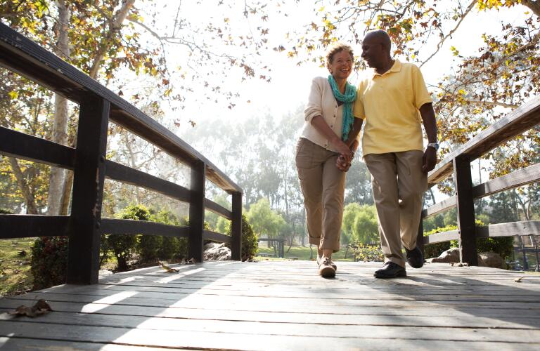 senior couple walking over bridge
