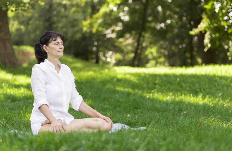 woman meditating in field outside
