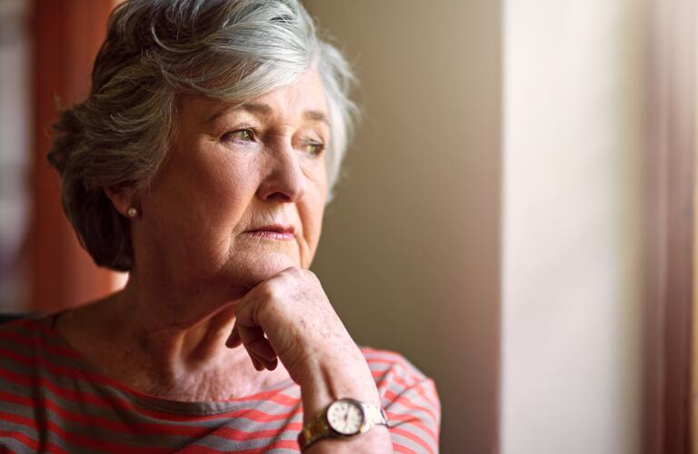 Senior Caucasian woman looking out window in deep thought or concern