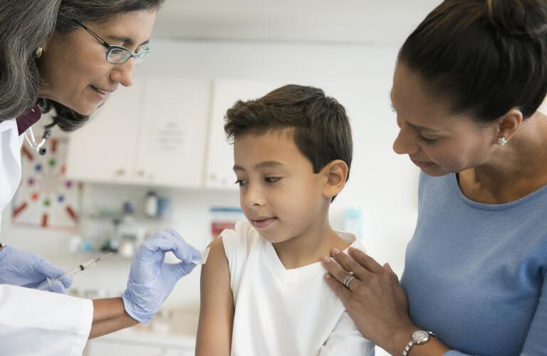 Young Hispanic boy getting vaccination or flu shot from pediatrician or nurse