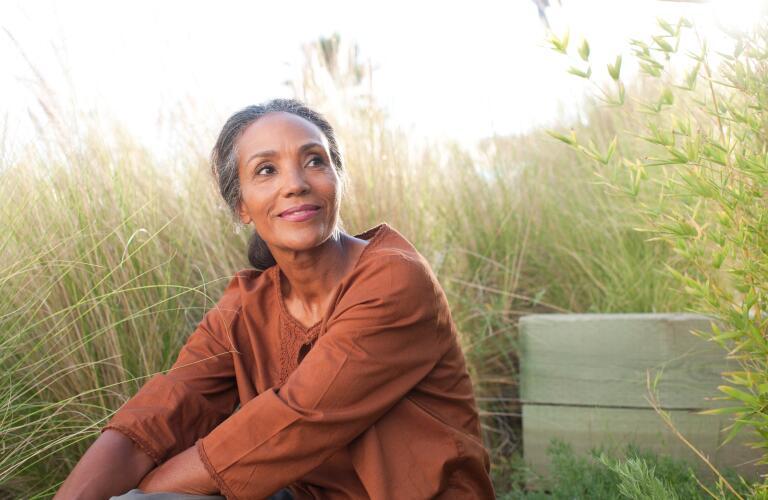 serene woman sitting outside in field
