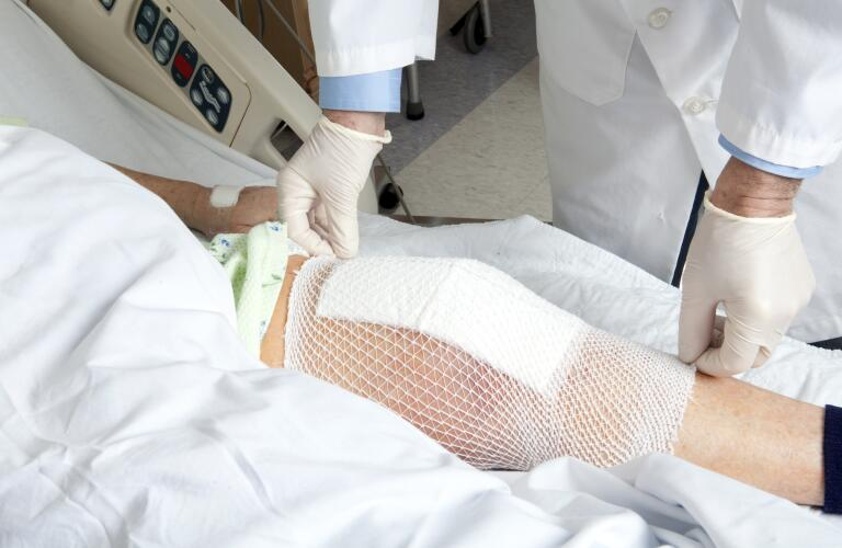 Unseen patient in hospital bed with knee replacement bandage