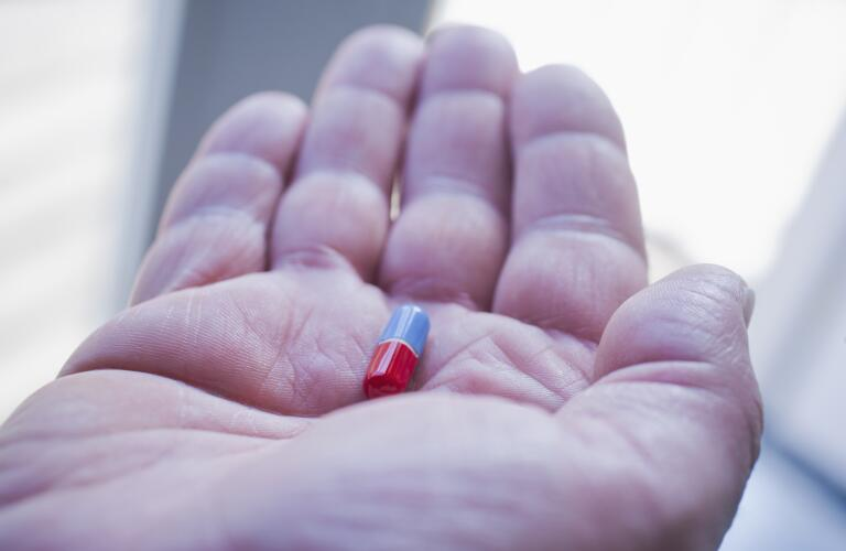 close up of hand holding pill