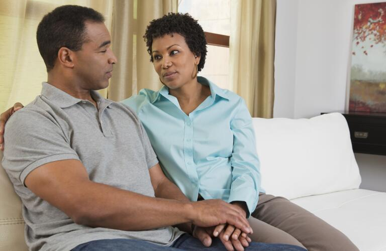 couple-having-discussion-on-couch