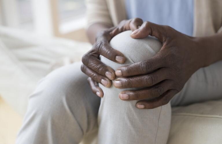 Close-up of unseen African American woman's hands holding knee in pain