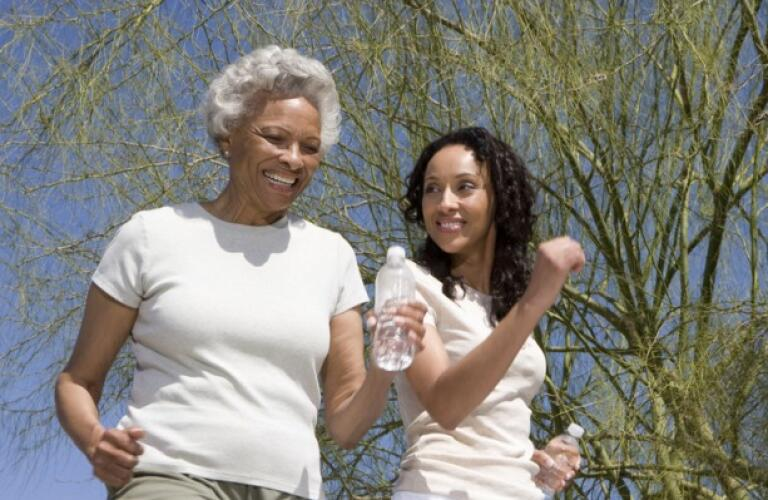 African american mother and daughter jogging together against blue sky