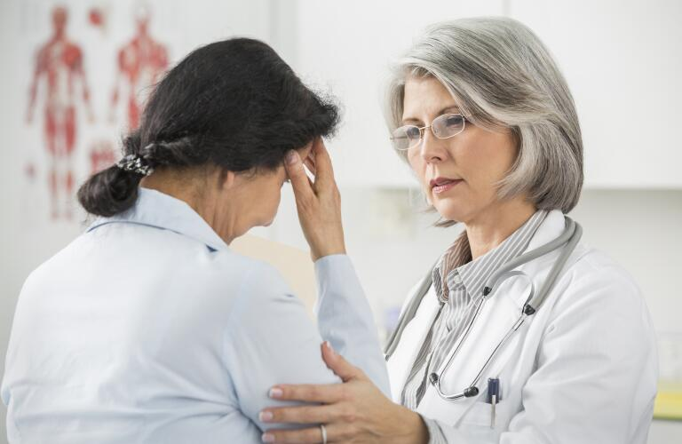 Female Caucasian doctor comforting patient with head pain