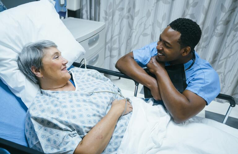 Young male African American doctor or nurse talking to older female Caucasian patient in hospital bed