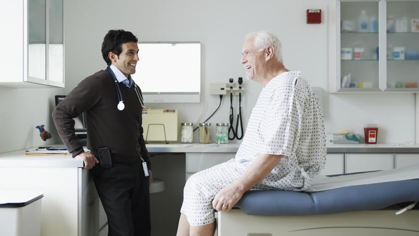Senior male patient in hospital gown talking to male doctor