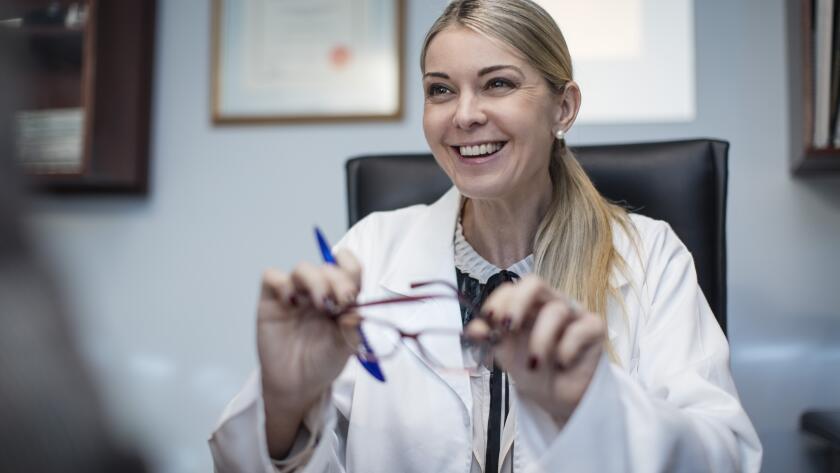 portrait of smiling Caucasian female eye doctor at desk holding eye glasses and pen