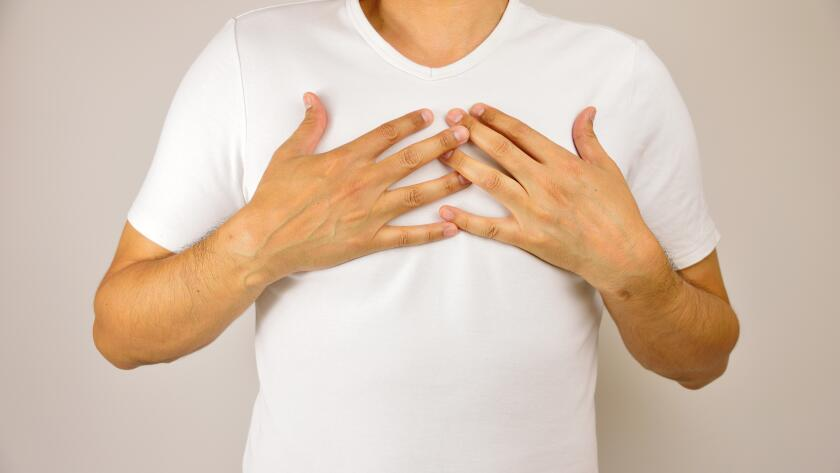 man with hands on chest