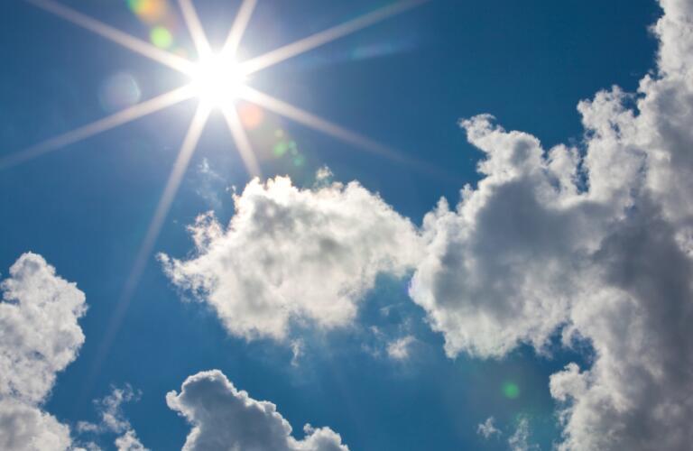 Cumulus clouds with sun flare