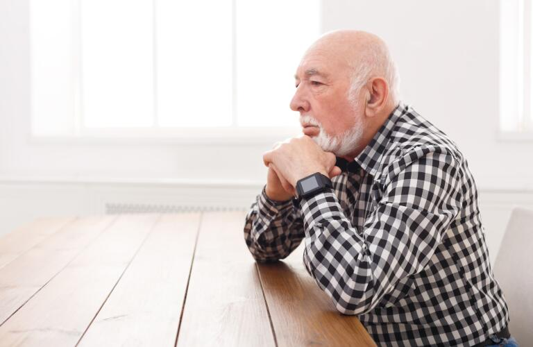 concerned senior man sitting at table