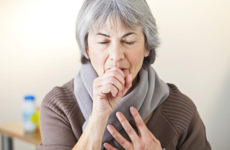senior woman coughing in hand
