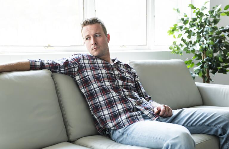 depressed male sitting on couch looking away