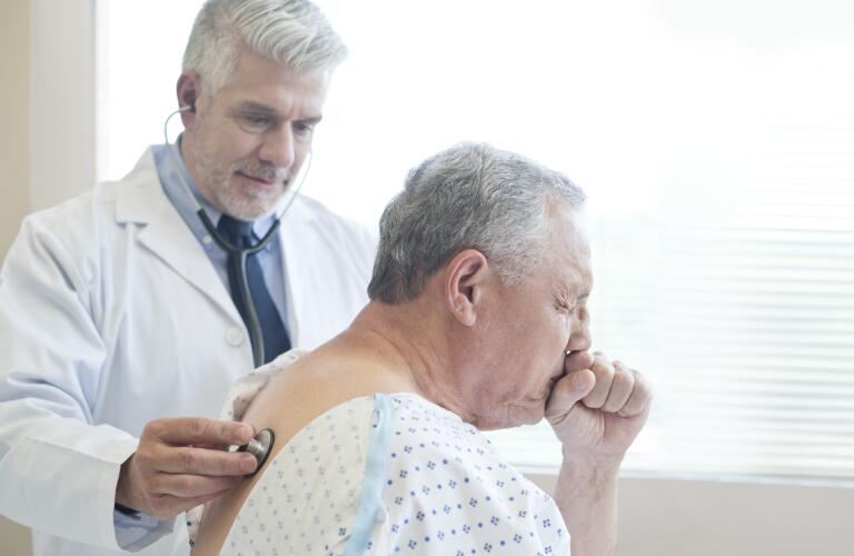 Senior Caucasian man coughing during doctor's exam while doctor checks back with stethoscope