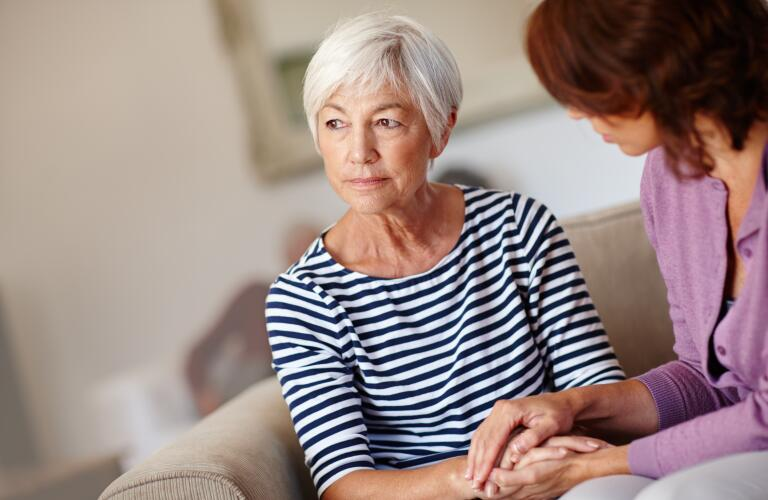 senior woman holding hands of caregiver