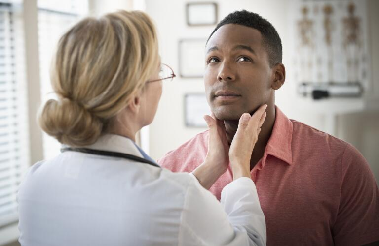 Doctor examining man's neck