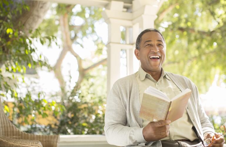 laughing-senior-man-reading-on-porch