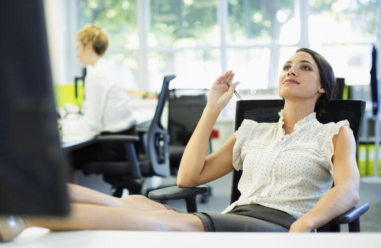 woman daydreaming at office desk