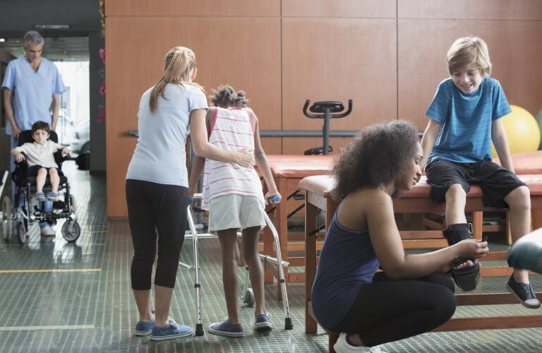 physical therapists helping children, one with a medical walker (walking aid)