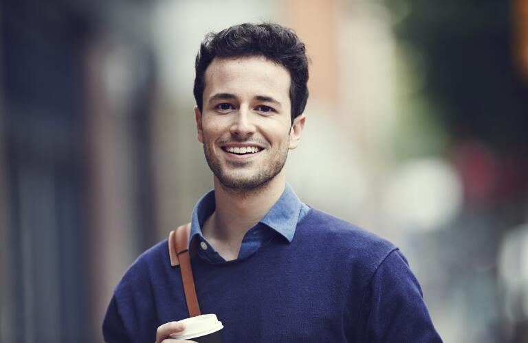 portrait-of-smiling-young-man-carrying-bag