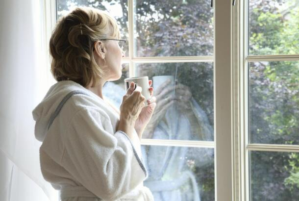 Woman Drinking Coffee Looking Out Window