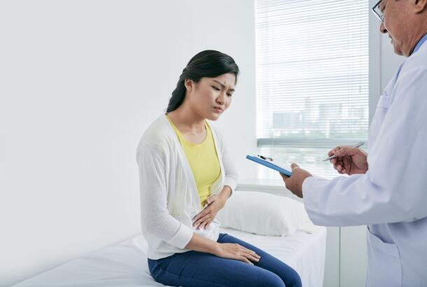 Young Asian woman suffering from stomach pain talking to doctor