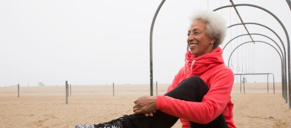 african american senior woman stretching on beach