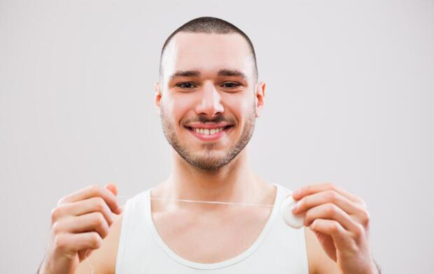 smiling man holding up dental floss