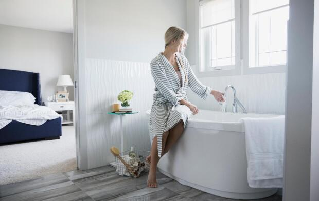 woman in bathrobe filling up bathtub
