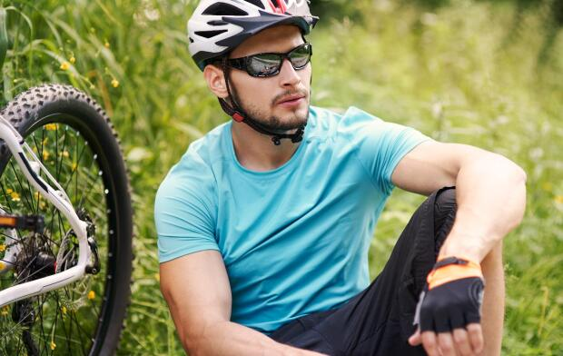 biker wearing sunglasses sitting down in grass