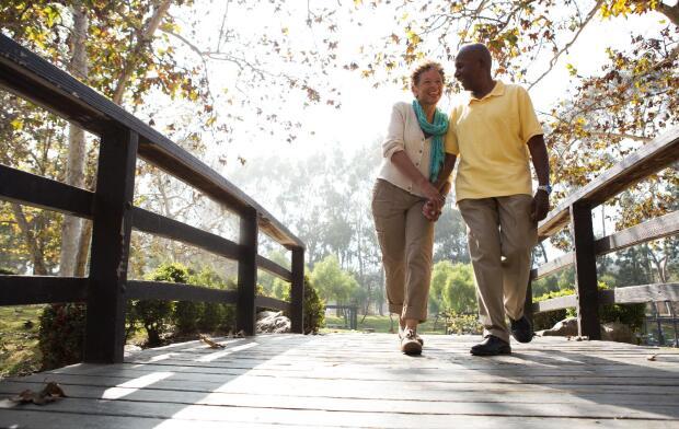 senior couple walking over bridge