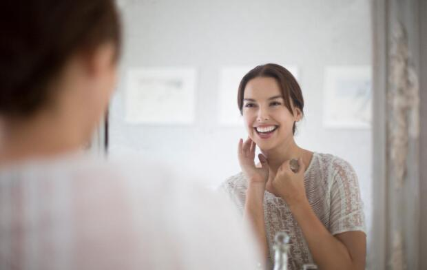woman smiling at reflection in bathroom mirror