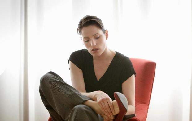 Caucasian woman sitting in chair removing high heel and rubbing foot
