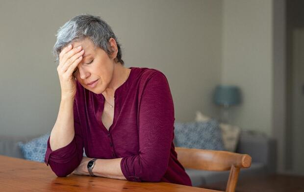 Senior Caucasian woman at table with head on hand from stress, fatigue or migraine headache