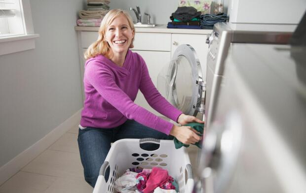 smiling woman in front of washing machine with basket of clothes