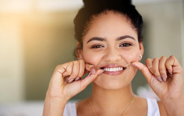 smiling woman flossing teeth