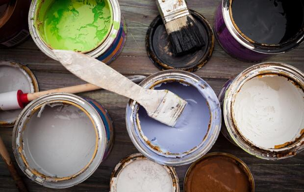 group of colorful open paint cans with brush