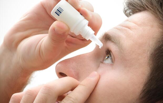 Man using eye drops