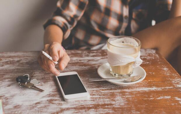 Woman holding cigarette with coffee and phone